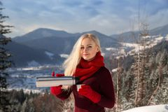 Beautiful blonde girl with hot drink in winter. Stock Photography