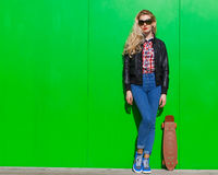 Beautiful blonde girl in huge sunglasses and a black jacket posing nex to green wall on a sunny day with a small skateboard Royalty Free Stock Photos