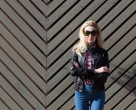 Beautiful blonde girl in huge sunglasses and a black jacket posing nex to wooden wall on a sunny day Stock Photography