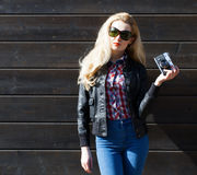Beautiful blonde girl in huge sunglasses and a black jacket posing nex to wooden wall on a sunny day with a vintage camera Royalty Free Stock Photos