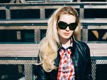 Beautiful blonde girl in huge sunglasses and a black jacket sitting on the steps of a sunny day Royalty Free Stock Image