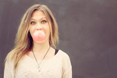 Beautiful blonde girl inflates a red bubble from chewing gum. Close up. Outdoor Royalty Free Stock Photo