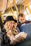Beautiful blonde girl in leather jacket reading book. In bus Royalty Free Stock Image