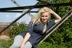Beautiful blonde girl lies on a construction site Stock Photo