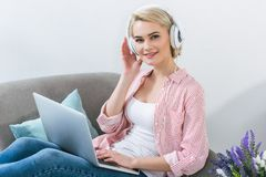 Beautiful blonde girl listening music with headphones. And using laptop Stock Photo