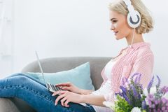 Beautiful blonde girl listening music with headphones and using laptop. At home Stock Images