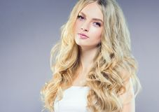 Beautiful blonde girl with long curly hair over purple background. Studio shot royalty free stock photography