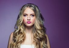 Beautiful blonde girl with long curly hair over purple background. Studio shot royalty free stock image