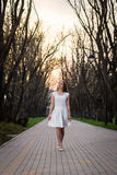 Beautiful blonde girl with long wavy curls in a white dress walk in evening the park among big trees. Stock Photography