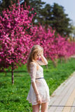 Beautiful blonde girl with long wavy curls in a white dress walk in the park among the pink trees, stunning makeup. Beautiful blonde girl with long wavy curls in stock photo