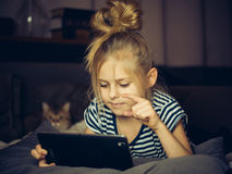 Beautiful blonde girl looking Tablet with cat. Royalty Free Stock Image