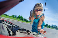 Beautiful blonde girl looking under the hood of the car. Sad attractive blonde in front of her car broken down car, assistance concept. Upset woman emotionally Royalty Free Stock Photography