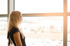 Beautiful blonde girl looks into the large panoramic windows to street royalty free stock photography
