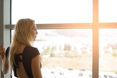 Beautiful blonde girl looks into the large panoramic windows to street stock image
