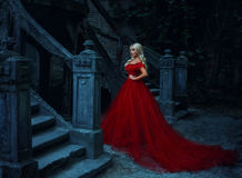 Beautiful blonde girl in a luxurious red dress. Beautiful blonde girl with long hair. She is in a luxurious red dress. Queen walks near her castle. Vampire stock photography