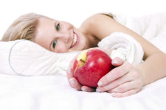 Cheerful girl in lingerie on the bed, an apple in his hand. Stock Images