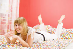 Beautiful blonde girl lying on bed and smiling. Beautiful blonde girl lying on the bed. Blanket with butterflies. She dressed in white. Bedroom is red Royalty Free Stock Image