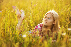 Beautiful blonde girl lying in the grass Royalty Free Stock Photography