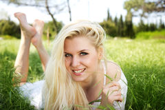 Beautiful blonde girl lying in green field Stock Images