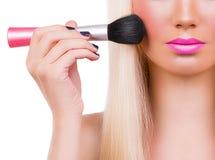 Beautiful blonde girl with makeup brush Royalty Free Stock Photo