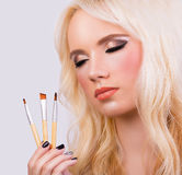 Beautiful blonde girl with makeup brushes Stock Image