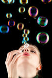 Beautiful blonde girl making colorful soap bubbles royalty free stock photo