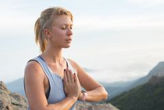 Beautiful blonde girl meditating on the top of the high rocky mountain in Malibu, USA. Beautiful blonde girl meditating on the top of the high rocky mountain in Royalty Free Stock Images
