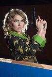 Beautiful blonde girl in military khaki shirt with gun Royalty Free Stock Photos