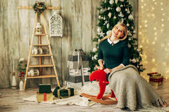 Beautiful blonde girl is opens the gift at Christmas Royalty Free Stock Photography