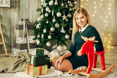 Beautiful blonde girl is opens the gift at Christmas Stock Photo