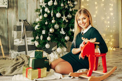 Beautiful blonde girl is opens the gift at Christmas Royalty Free Stock Photos