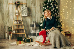 Beautiful blonde girl is opens the gift at Christmas Royalty Free Stock Photo