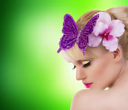 Beautiful blonde girl with orchid flower and butterfly Royalty Free Stock Image