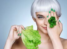 Beautiful blonde girl with parsley and lettuce leaves in her hand royalty free stock photos