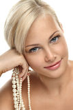 Beautiful blonde girl with Pearl beads. Image with beautiful blonde smiling girl with Pearl beads on white background close-up Stock Images
