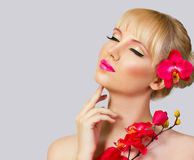 Beautiful blonde girl with perfect makeup on grey background Royalty Free Stock Photo