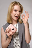 Beautiful blonde girl with pink camera laughs and smiles. On the gray background. Concept of the beauty Stock Photo