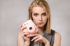 Beautiful blonde girl with pink camera laughs and smiles. On the gray background. Concept of the beauty Stock Image