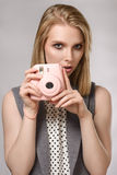 Beautiful blonde girl with pink camera laughs and smiles. On the gray background. Concept of the beauty Stock Images