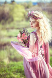 Beautiful blonde girl in a pink dress. Portrait of a beautiful blonde girl in a pink dress with long developing a bouquet of flowers in their hands Royalty Free Stock Photography