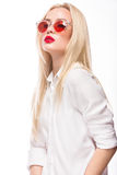 Beautiful blonde girl in pink glasses and shirt. Beauty face. Isolated on white background. Stock Photos