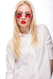 Beautiful blonde girl in pink glasses and shirt. Beauty face. Isolated on white background. Stock Photo