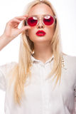 Beautiful blonde girl in pink glasses and shirt. Beauty face. Isolated on white background. Royalty Free Stock Images