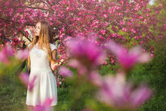 Beautiful blonde girl in pink peach and sakura garden. Beautiful girl outdoors spring portrait, young woman with flowers Stock Photos