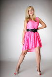 Beautiful blonde girl in pink summer dress. Beautiful blonde girl in full length in pink summer dress. Studio shot on gray background Stock Image