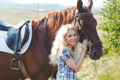 Beautiful blonde girl in plaid shirt hugging her brown horse stock images
