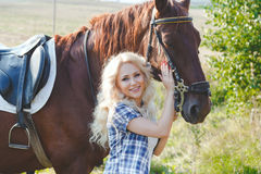 Beautiful blonde girl in plaid shirt hugging her brown horse stock photography