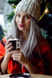 Beautiful blonde girl in pom pom hat and red scarf with wine red lips drinking coffee, looking at the camera Royalty Free Stock Photo