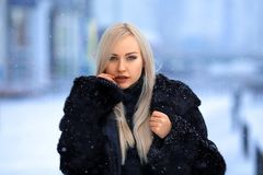 Beautiful blonde girl portrait under the snow royalty free stock photos