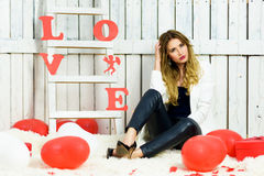 Beautiful blonde girl portrait on Valentines Da. Y. Being upset or irritated expression. Blue eyes and red lips wearing in a white jacket. Romantic scene. Red stock photography